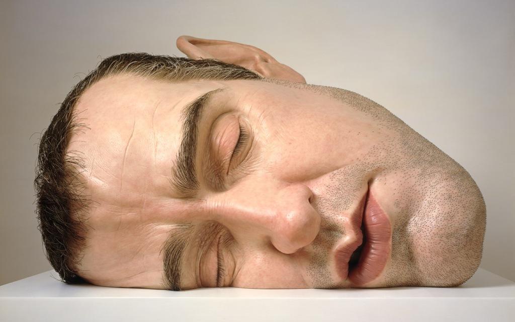 Escultura hiper-realista de Ron Mueck de uma uma cabeça de homem tamanha gigante